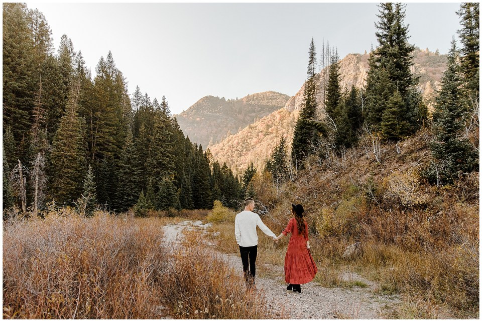 man holds hands with his fiance as they walk a trail during their Big Cottonwoon Canyon Engagement Session