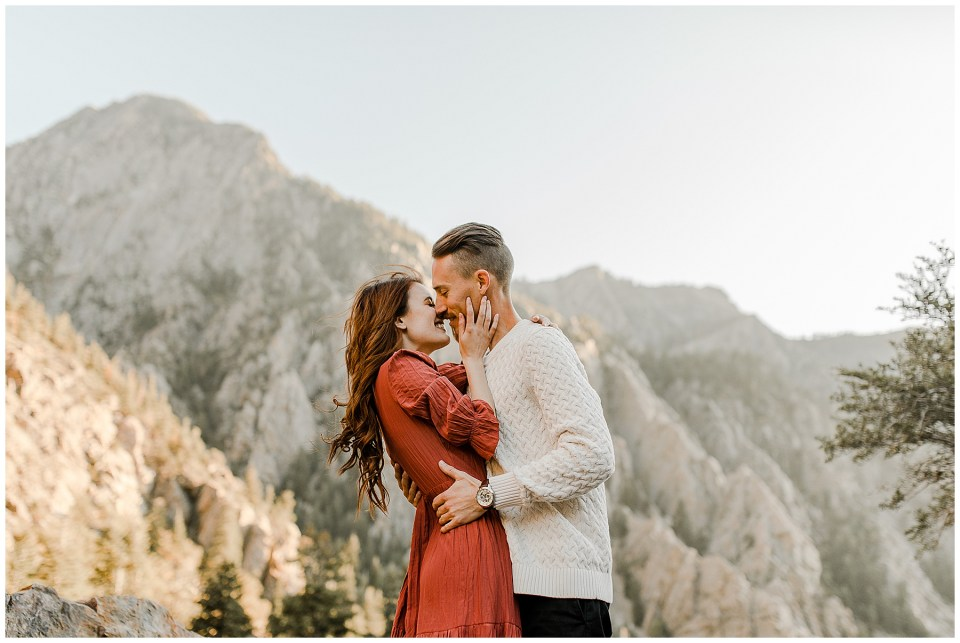 man kisses his fiance in front of an amazing mountain backdrop during their Big Cottonwood Canyon Engagement Session