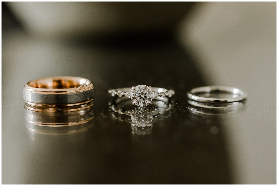 wedding rings on a table as a couple celebrated during their Adventurous Beach Elopement in Carlsbad, California
