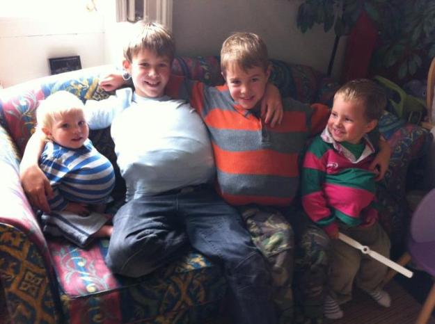 A picture of four young boys on a sofa with stuffed jumpers to appear pregnant - children of Breech Birth Director, Shawn Walker