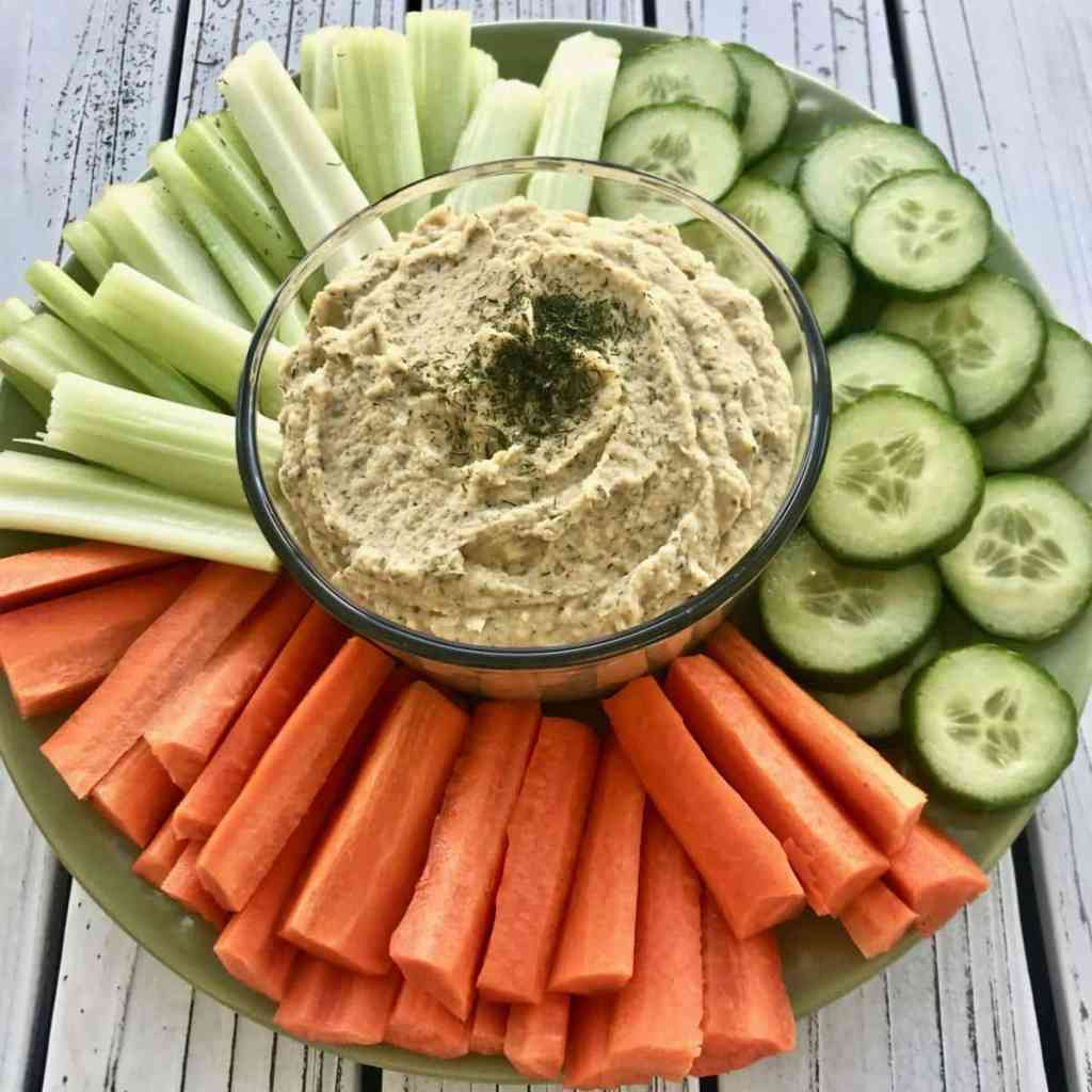 Dill pickle hummus in a glass bowl, surrounded by carrots, celery, and cucumber slices.