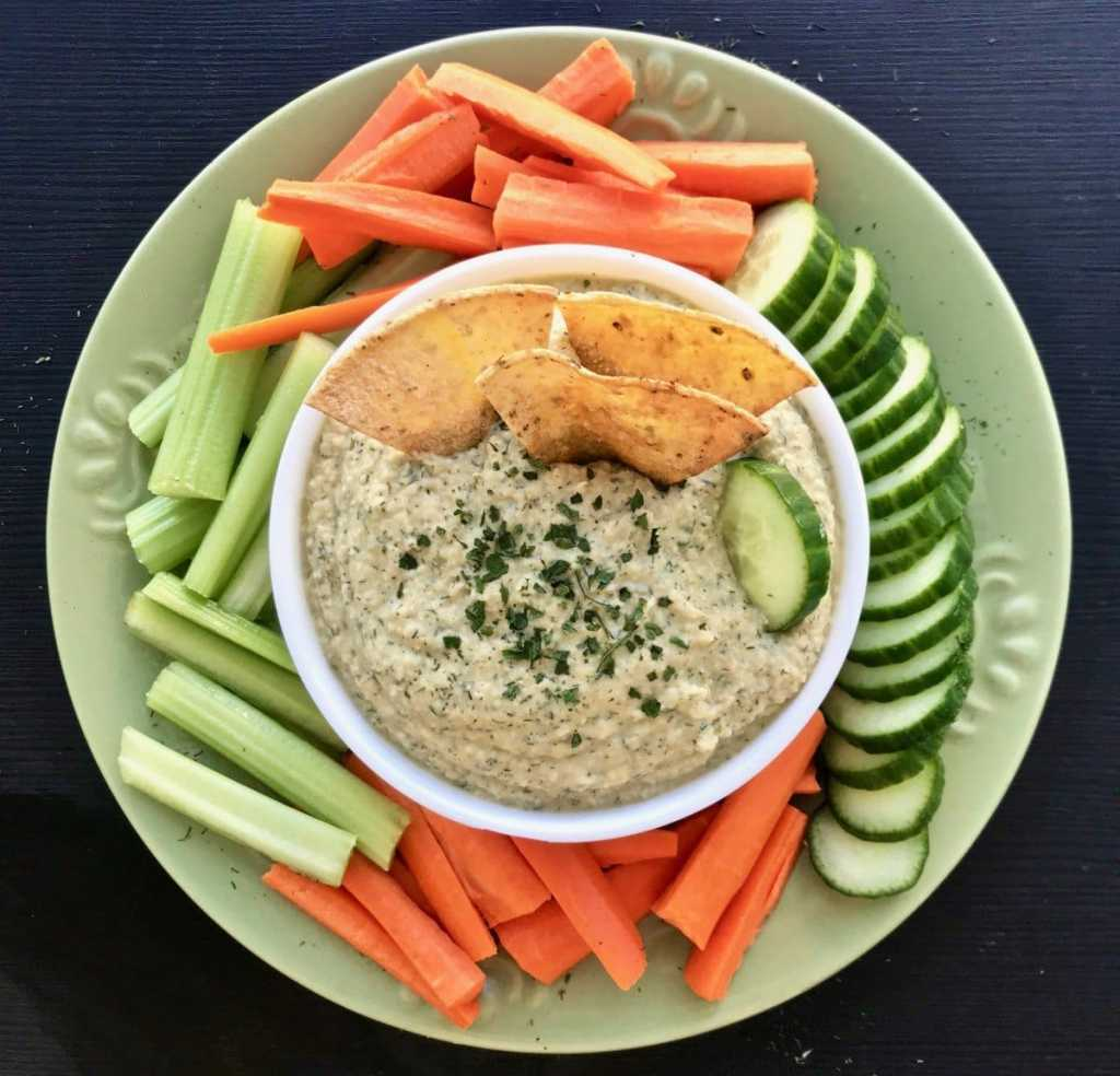 A plate of raw vegetables with a bowl of dill pickle hummus in the center.