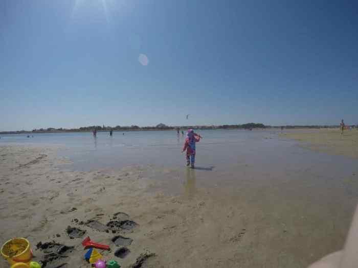Kleinkind läuft im Sand am Strand Richtung Meer - Strandurlaub in Kroatien mit Kleinkind - Ninska Laguna Beach