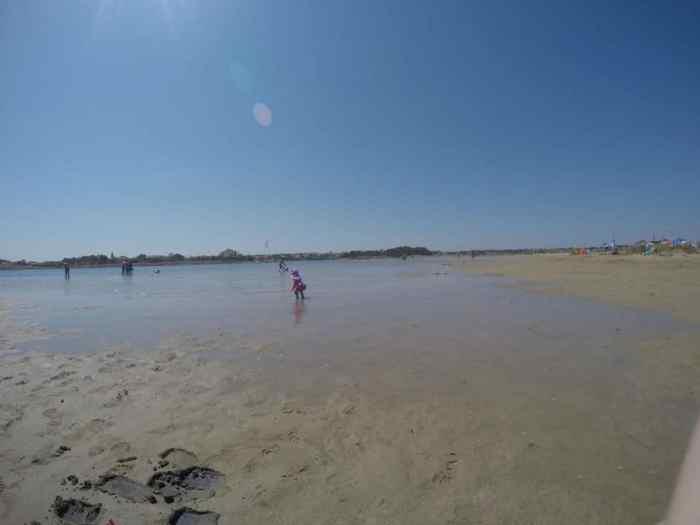 Mädchen läuft im Sand ans Meer, weiter Sandstrand un dflaches Wasser - der perfekte Kinder Strand in Kroatien in Nin - Ninska Laguna