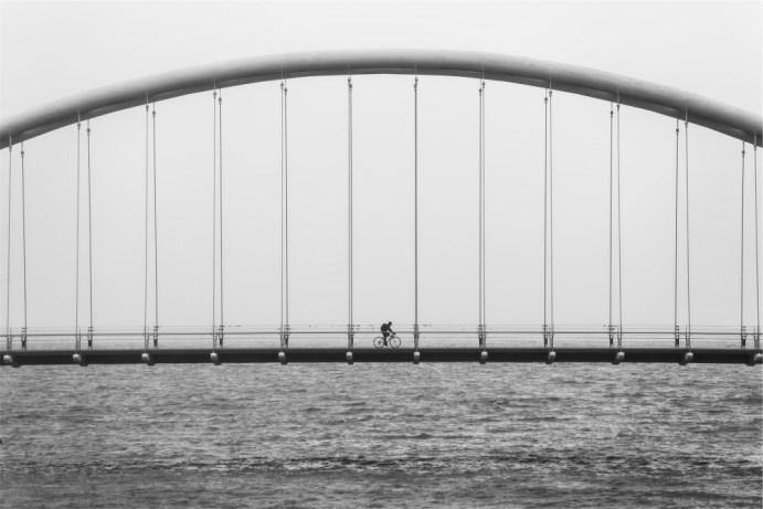 biking alone over bridge