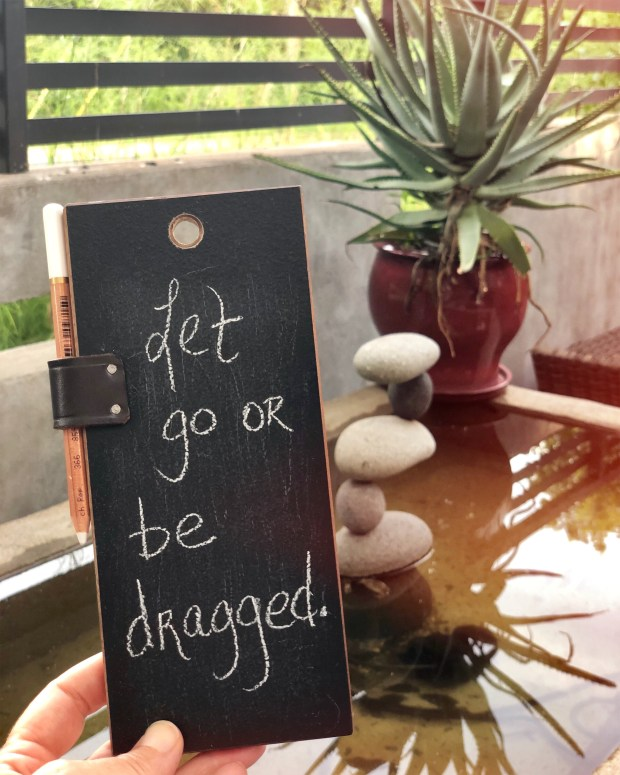 Chalkboard with Let go or be dragged written on it.