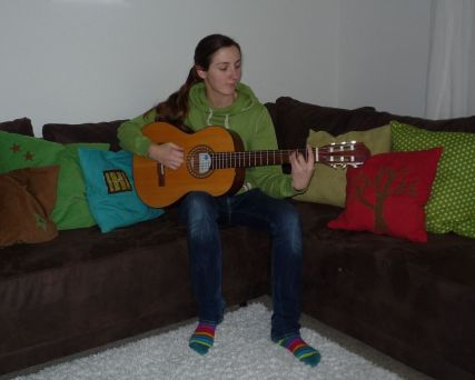 Brennender Schuh - Gitarre spielen auf dem Sofa zwischen selbstgenähten Kissen