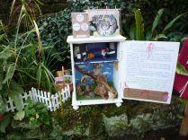 Brennender Schuh - Ausstellung in einem kreativen Garten in Gemünden, Geschichte in einem kleinen Zauber-Schrank