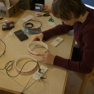 Jamison moves the coils to see where they can be and still have the LED light up.