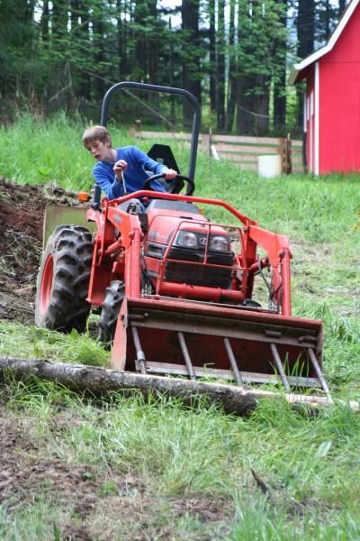 Jamison pushing a log around