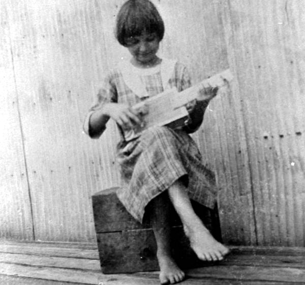May Newman playing a Cigar Box Guitar she made in the 1909