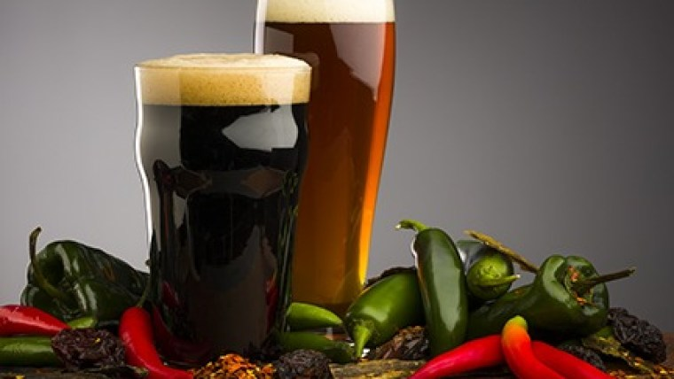 Two glasses of beer and small peppers