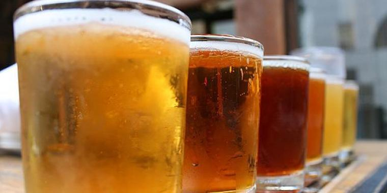 Five glasses of beer with different type of beer in each one.