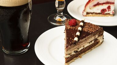 A glass of chocolate lager with a piece of chocolate cake.