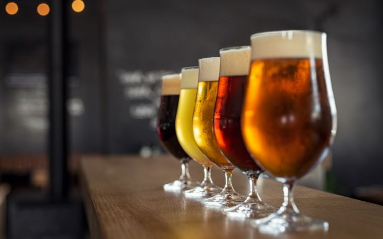 Row of beer glasses with different types of beer in them.