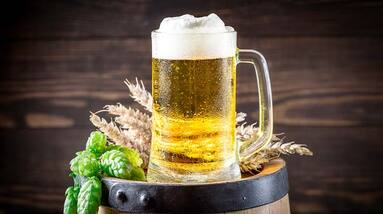 A mug of American light lager beer on a wooden cask with whats and hop flowers