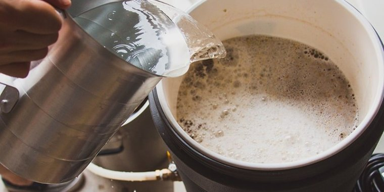 Pouring hot water into a beer wort