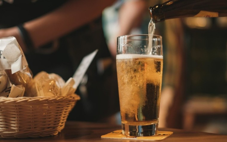 Pouring beer from the bottle to a glass with a basket of papers on the same table as the glass.