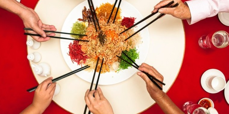 People eating with chopsticks from the same plate.