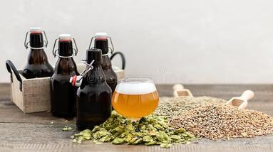 3 Bottles of homemade beer with a glass of beer some dry what and hop flowers.