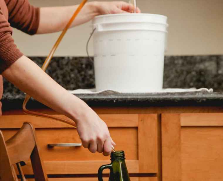 Transferring beer from beer bucket to a glass bottle.