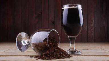 A glass of porter beer and a knocked glass of dark roasted malt spilling on the table.
