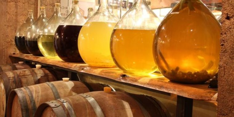 A row of glass mead bottles at the top and a row of wooden barrels at the bottom.