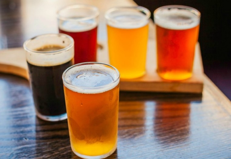 Five glasses of beer with different colors and flavros.