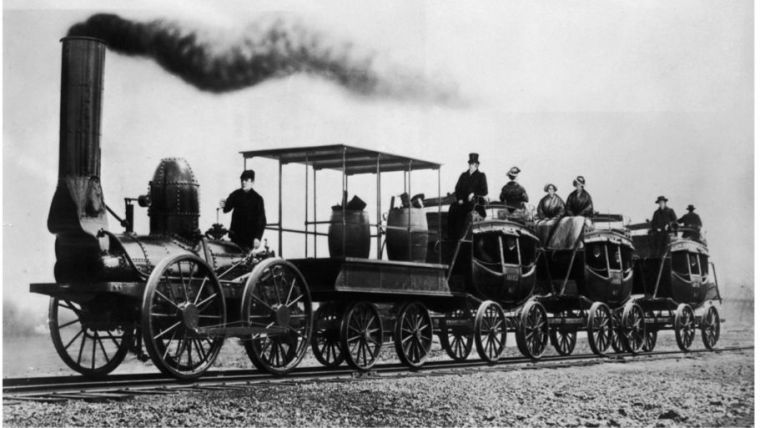 An old black and white photo showing a steam train at the beginning of Industrial Revolution.