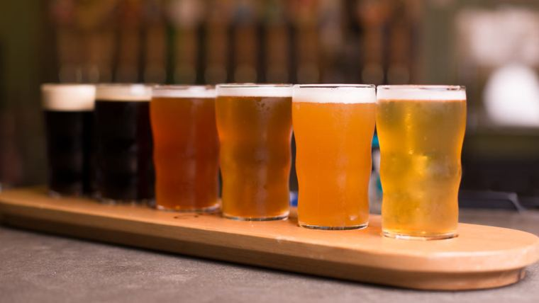 Glasses with different beer styles positioned by darkest to lightest color.