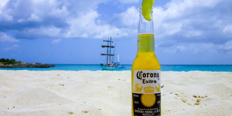 A bottle of Corona with a piece of lime on a sandy beach.