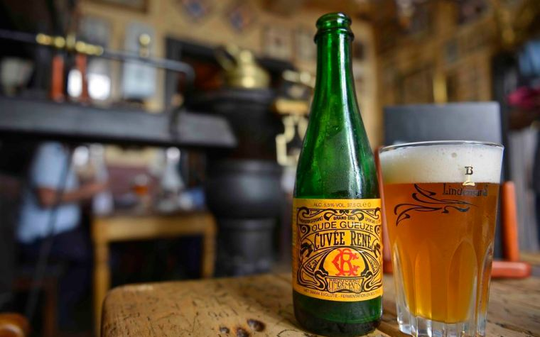 A bottle and a glass of lambic beer on a table inside a pub.