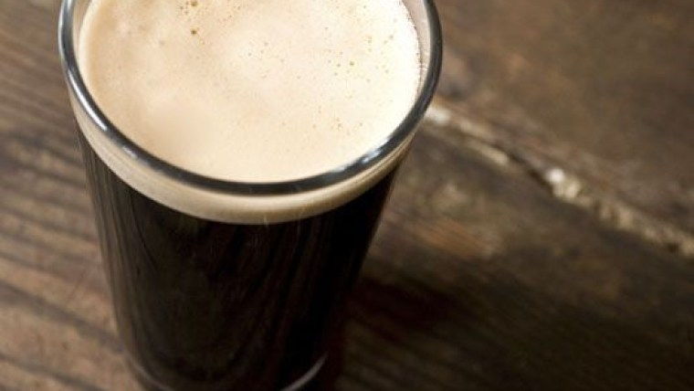 A glass of Irish stout beer on a wooden table.