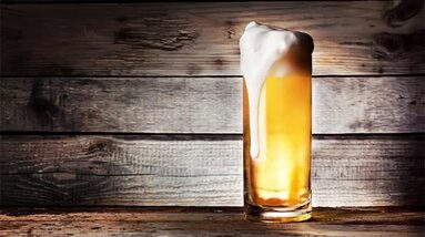 a glass of Kolsch beer in front of a wooden background
