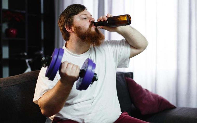 A man drinking beer and lifting weights.