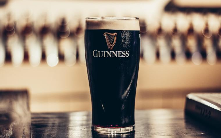 A glass of Guinness beer on a table.