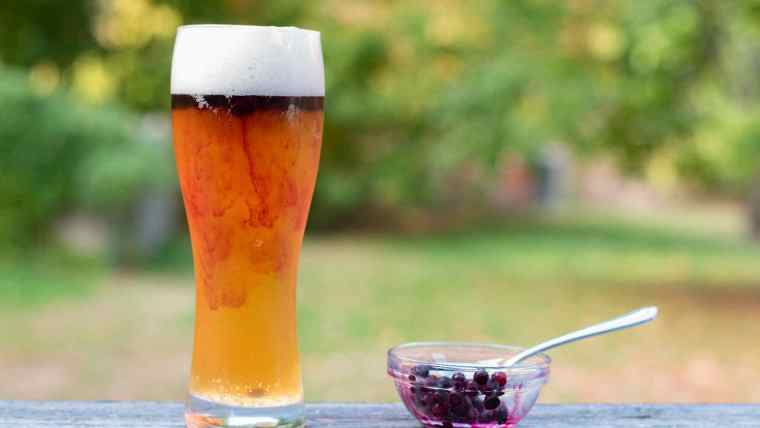 A glass of beer and a small bowl of fresh blueberries with a spoon.
