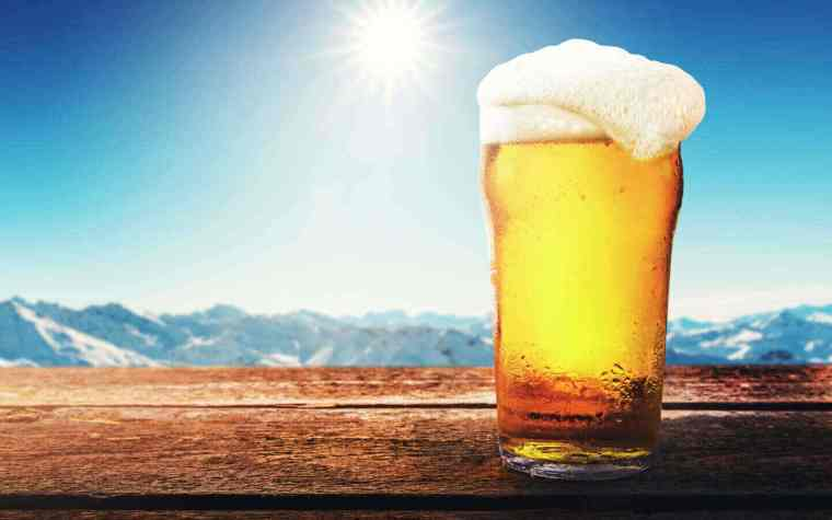 A glass of cream ale with a mountain range in the background.