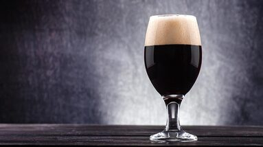 A glass of milk stout beer in the grey background