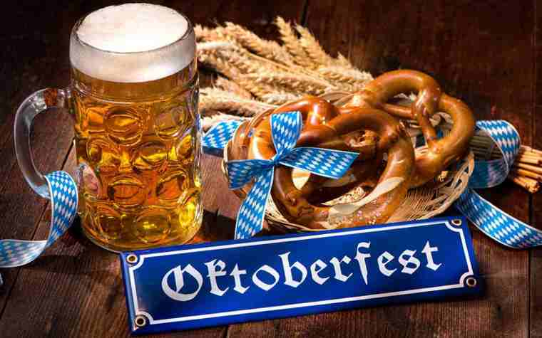 A mug of beer with large pretzels, dry wheat and an Oktoberfest sign.