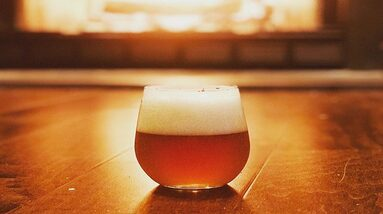 A glass of West Coast IPA beer style on a table.