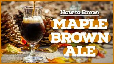 A glass of maple brown ale surrounded with fallen yellow leaves.