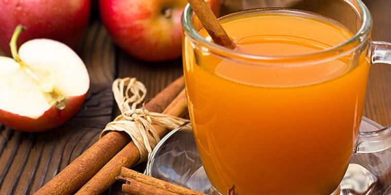 A cup of apple cider and stick of cinnamon, cloves and red apples on the table.