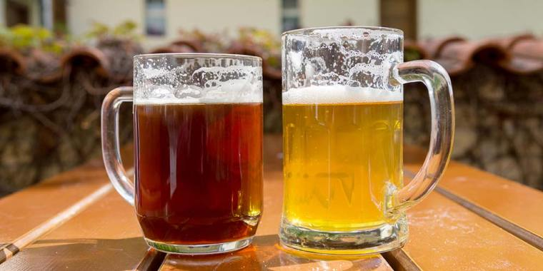 One mug of ale beer and one mug of lager beer on a wooden table.
