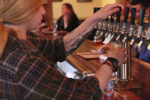 pouring a draft craft beer, tattoos arm