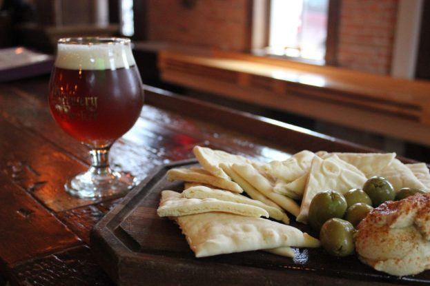 hummus pita olive plate and poured draft craft beer
