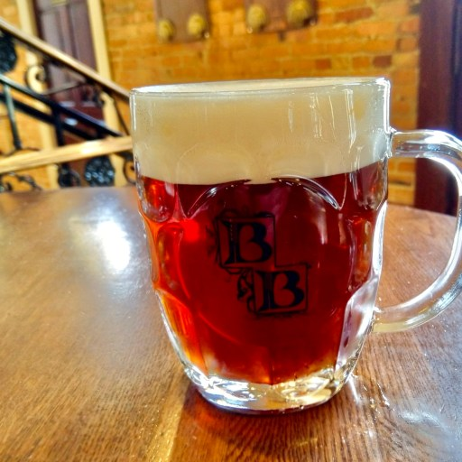fancy logo mug, brewery becker English Mild draft beer up close