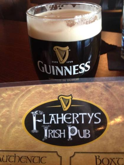 A pint of guiness and a menu from Flaherty's Irish Pub