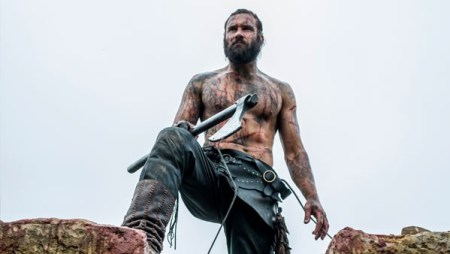 A blood covered viking standing atop a wall.