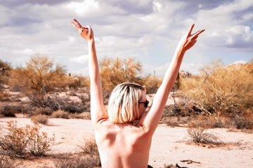 Kristen throws her hands up in the western US desert.